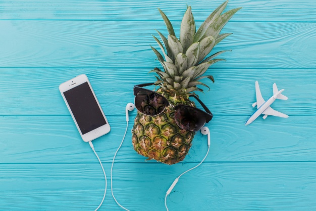zomer-samenstelling-met-ananas-zonnebril-en-mobiele-telefoon_23-2147631938